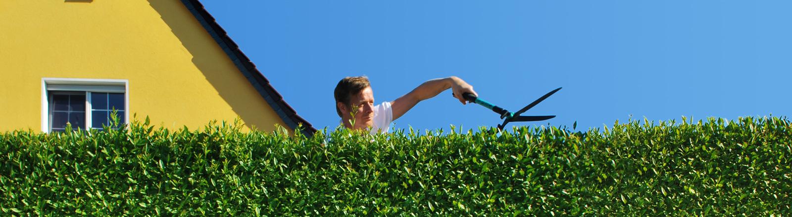 Mann schneidet Hecke vor Einfamilienhaus