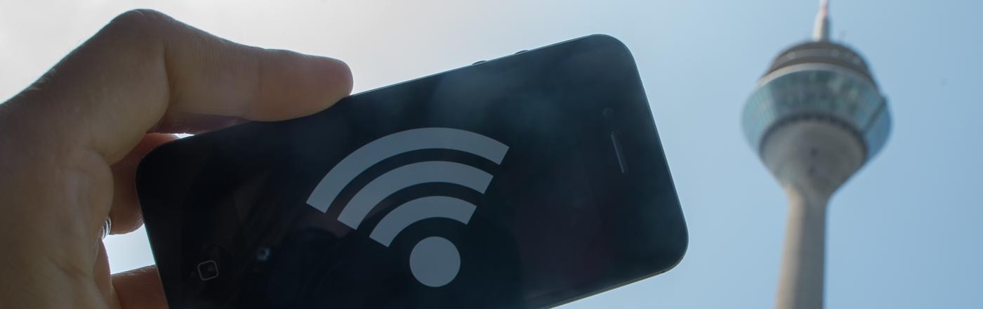 Ein WLAN-Symbol auf einem Smartphone, im Hintergrund der Düsseldorfer Rheinturm