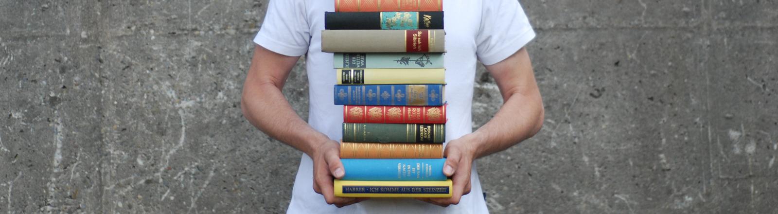 Jemand hält einen Stapel Bücher in den Händen.