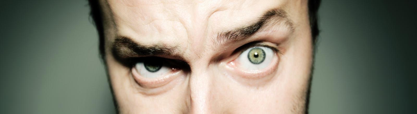 Ein Mann guckt zweifelnd mit hochgezogener Augenbraue