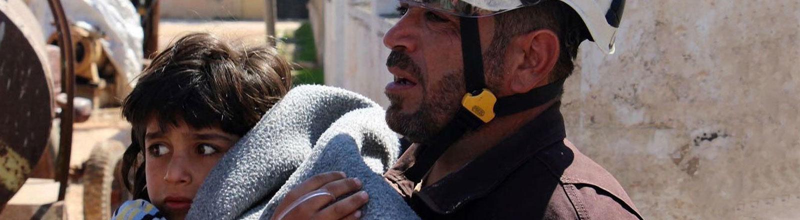 Ein von der «Syria Civil Defence» (Weißhelme) am 04.04.2017 zur Verfügung gestellte Foto, zeigt einen Freiwilligen Helfer, der ein Opfer eines mutmaßlichen Giftgasangriffs in Chan Scheichun, Syrien, versorgt. Bei einem Luftangriff mit Giftgas sind im Nordwesten Syriens Aktivisten zufolge mindestens 58 Menschen getötet worden, darunter elf Kinder. Die Syrische Beobachtungsstelle für Menschenrechte meldete aus dem Ort Chan Scheichun zudem Dutzende Verletzte.