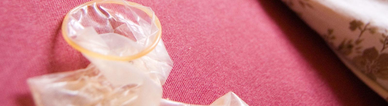 Ein leeres Kondom liegt neben einem Bett