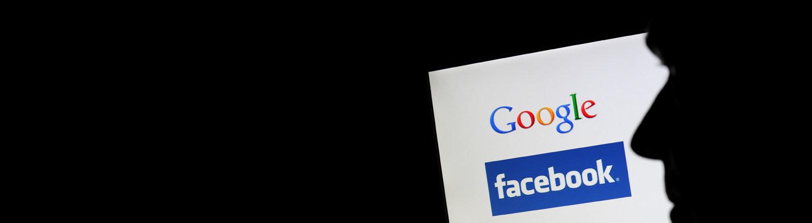 Ein Computerbildschirm mit den Logos von Google und Facebook, davor die Silhouette eines Mannes