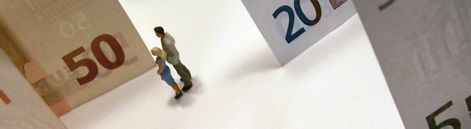 Schöne Eurowelt - Zwei Plastikfiguren (Mann und Frau) stehen inmitten von Geldscheinen
