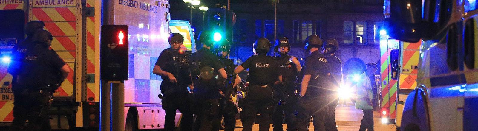 Bewaffnete Polizisten und Einsatzfahrzeuge mit Blaulicht an der Arena in Manchester.