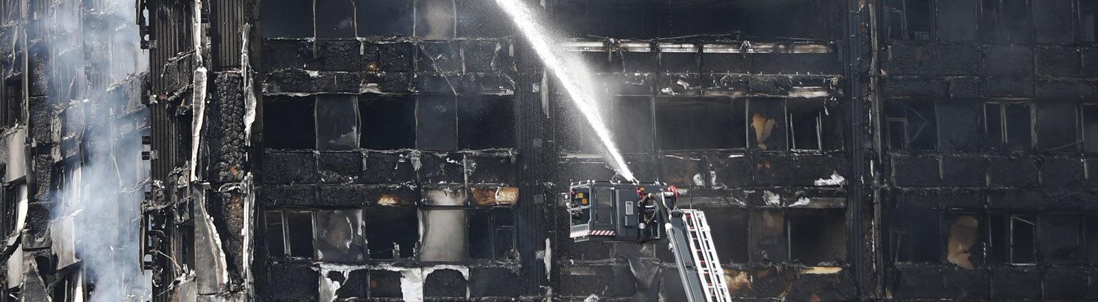 Feuerwehrleute spritzen am 14.06.2017 in London (Großbritannien) Wasser auf das noch rauchende Hochhaus. Bei dem Brand eines Hochhauses im Zentrum Londons sind mehrere Menschen ums Leben gekommen. Das Feuer war in der Nacht ausgebrochen, am frühen Morgen stand das Gebäude mit mehr als 20 Stockwerken noch lichterloh in Flammen.