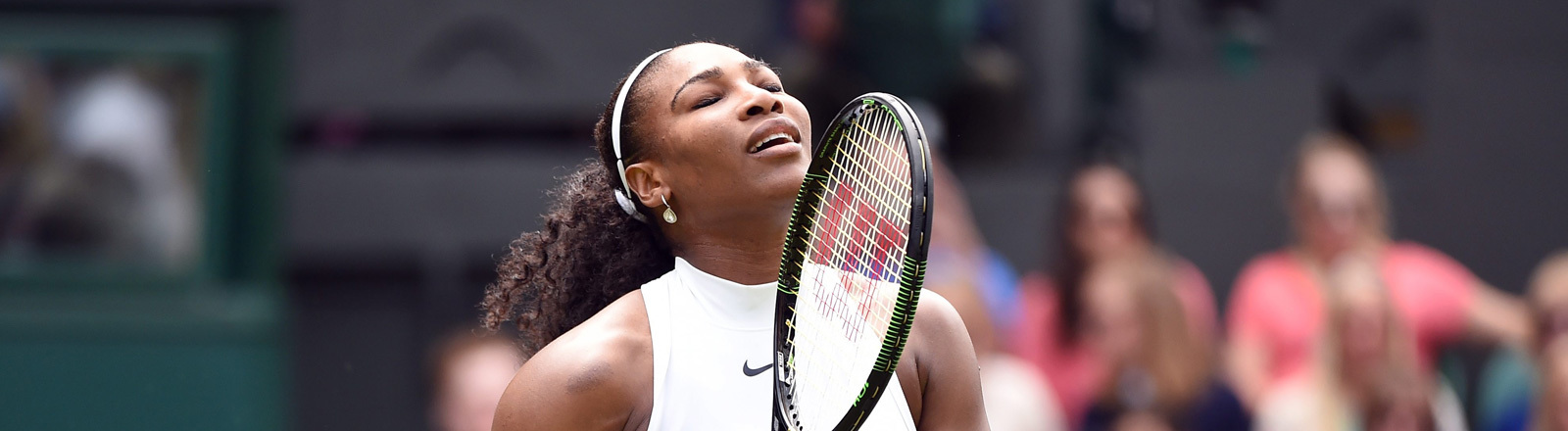 Serena Williams beim Wimbledon-Turnier mit Tennissschläger in der Hand und frustrierter Miene.