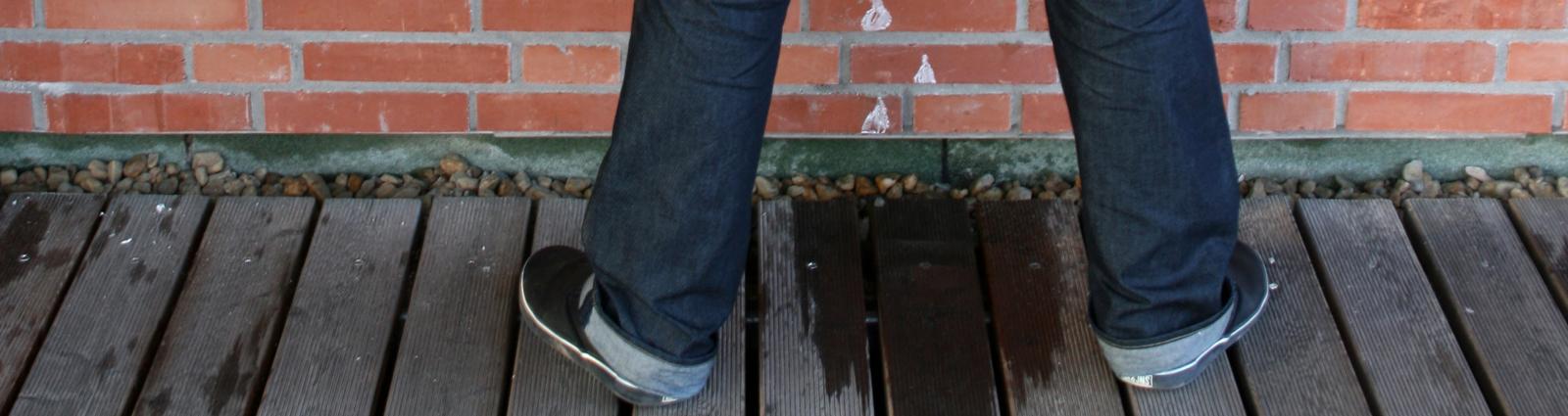 Mann uriniert an eine Mauer