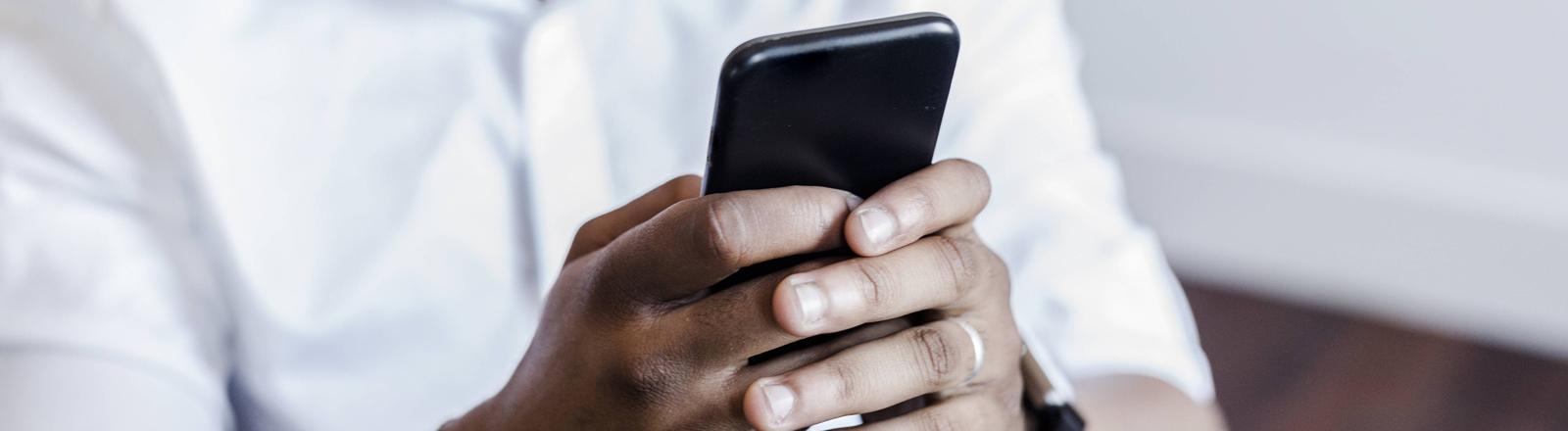 Mann hält Handy in der Hand