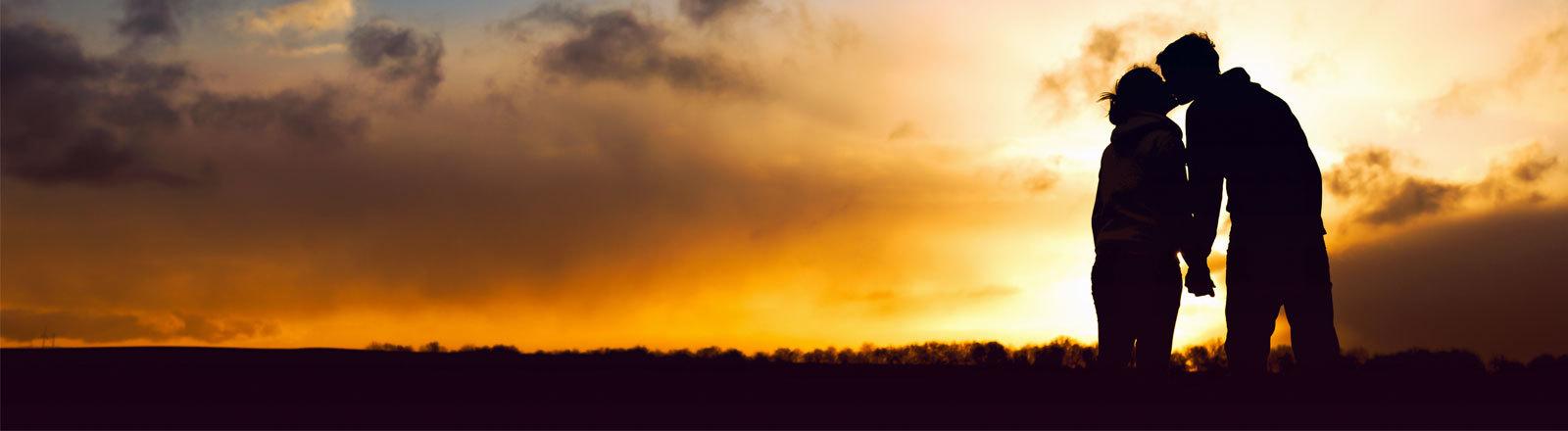 Zwei Menschen küssen sich im Sonnenuntergang
