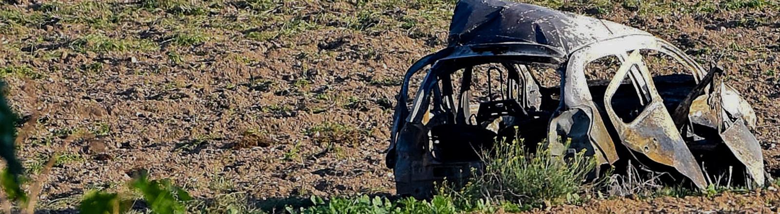 Ausgebranntes Auto auf Feld