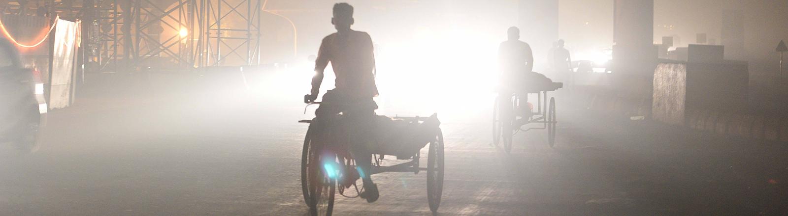 Ein Rikscha-Fahrer umhüllt von Smog in der indischen Hauptstadt Neu Delhi