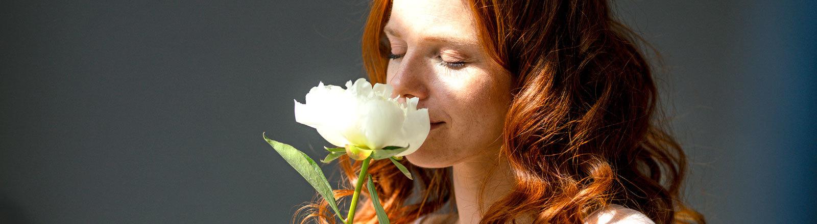 Rothaarige Frau riecht an weißer Blume.