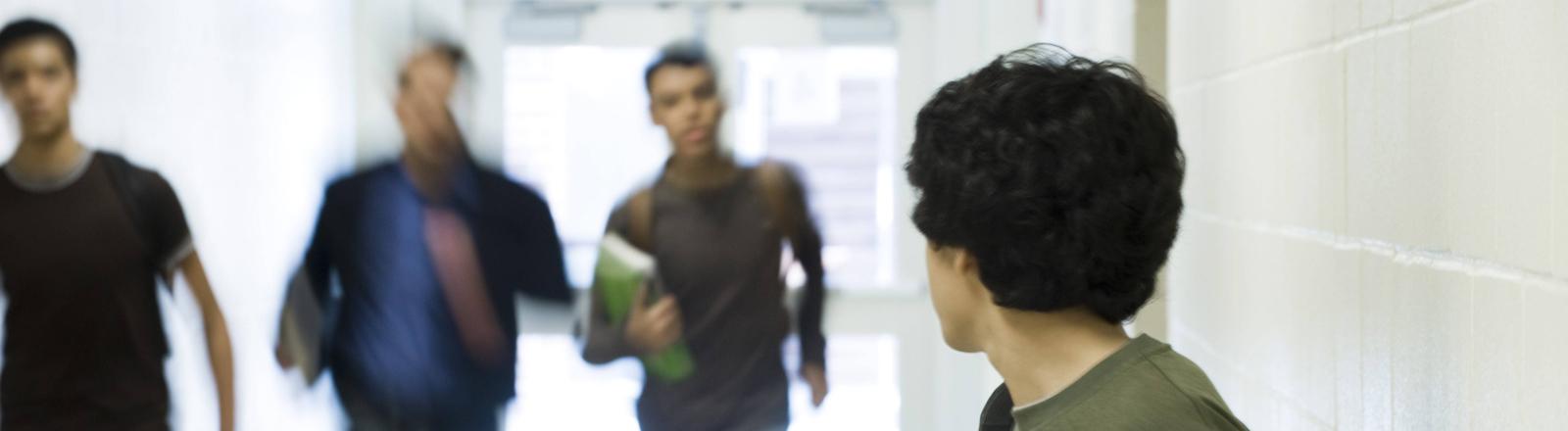 Zwei Schüler rennen aggressiv auf einen anderen zu.