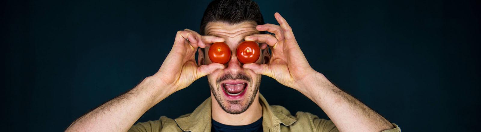 Ein Mann hält sich zwei Tomaten vor seine Augen.