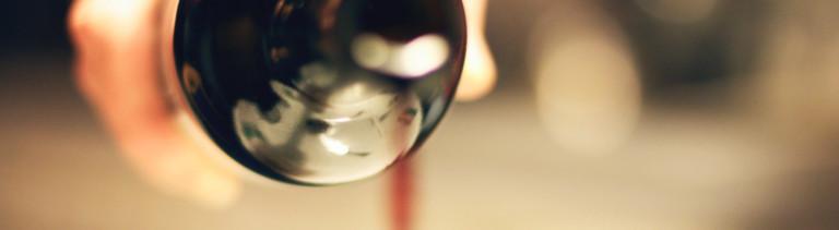 Eine Hand gießt Rotwein aus einer Glasflasche.