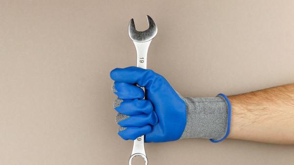 Eine Hand hält einen Schraubenschlüssel.