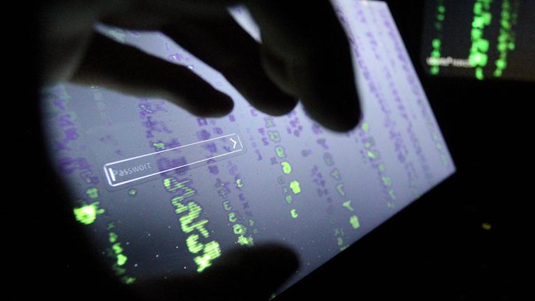 Cyberkriminalität: Eine Hand vor einem Monitor mit Password-Eingabefeld