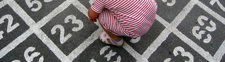Ein Mädchen steht auf Asphalt, auf dem Zahlenfelder aufgemalt sind.