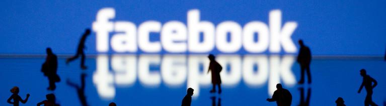 Schattenfiguren vor dem Facebook-Schriftzug.