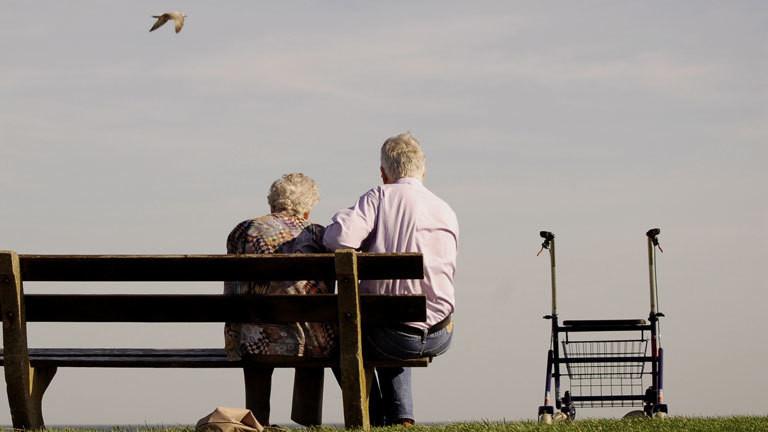 Alter Mann und alte Frau sitzen auf einer Bank, neben ihnen steht ein Rollator