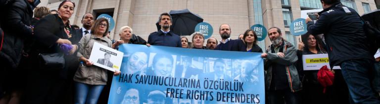 Menschenrechts-Aktivisten demonstrieren am 25.10.2017 vor einem Gericht in Istanbul (Türkei) mit einem Transparent mit Bildern der Angeklagten gegen den Prozess gegen elf Menschenrechtler, darunter auch der Deutsche Peter Steudtner (auf dem Banner der 2.v.r. unten). Die Staatsanwaltschaft wirft den Angeklagten «Mitgliedschaft in einer bewaffneten Terrororganisation» beziehungsweise «Unterstützung von bewaffneten Terrororganisationen» vor.