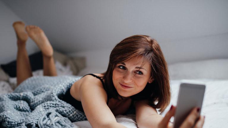 Frau auf dem Bett blickt ins Handy