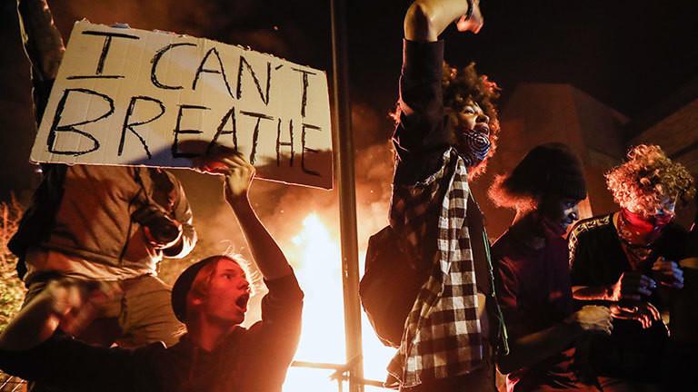 Demonstranten protestieren vor einem brennenden Polizeirevier in Minneapolis.
