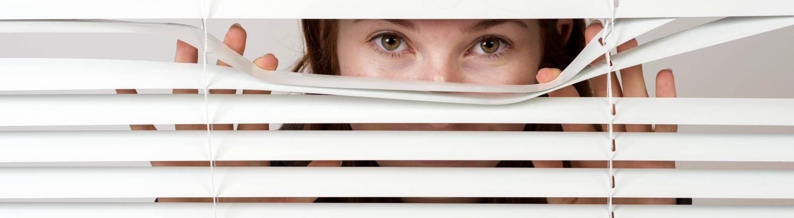 Eine Frau schaut neugierig durch den Schlitz einer Schalousie
