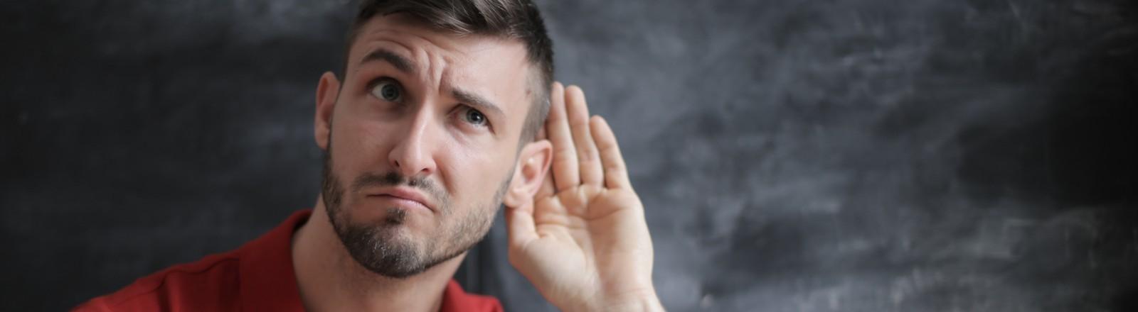 Ein Mann spitzt seine Ohren
