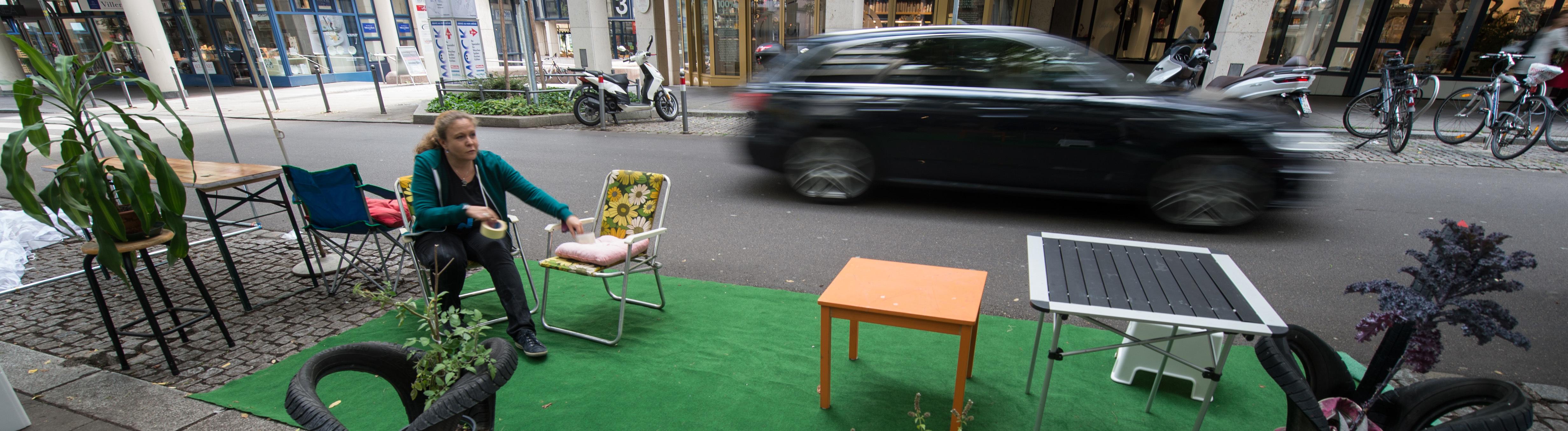 """Eine Aktivistin der Initiative """"Park(ing Day"""" arbeitet am 18.09.2015 in Stuttgart (Baden-Württemberg) an einem Mini-Park, der spontan und provisorisch für einen Tag auf einem Parkplatz entsteht."""