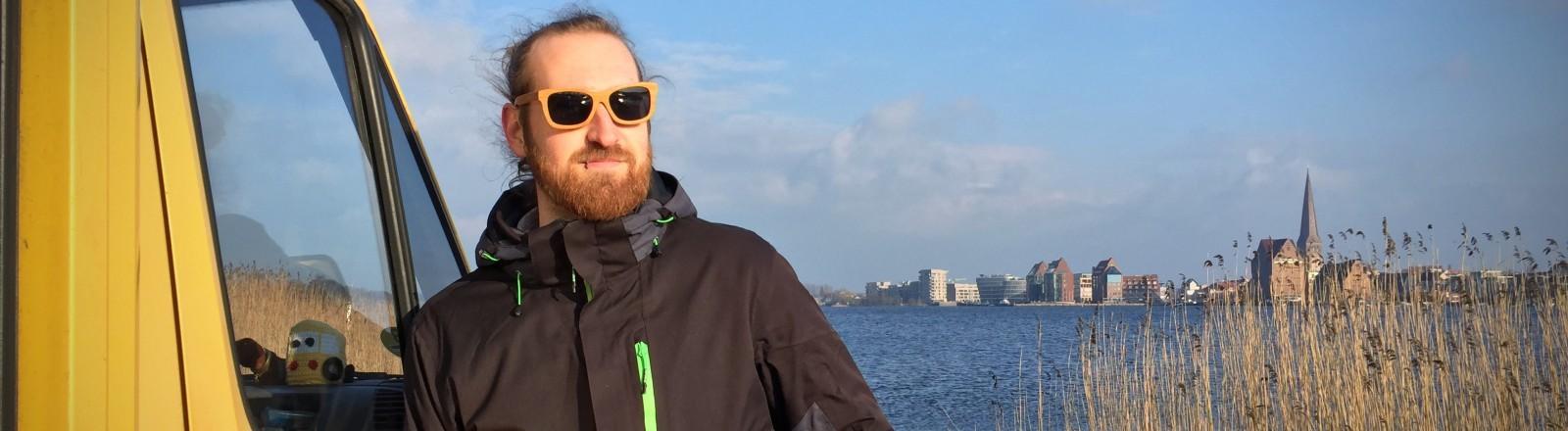 Ein Mann steht mit einem DHL-Laster am Ufer