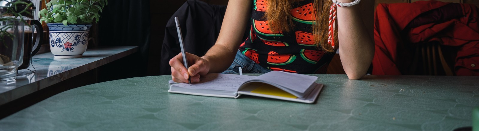Junge Frau schreibt in einen Planer.