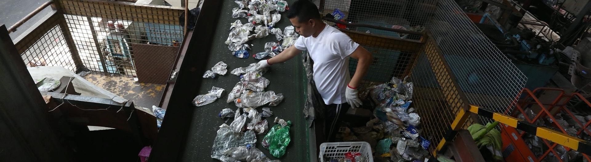 Mann sortiert Plastikflaschen in einer Recycling-Firma in Long Kwu Tan, 18.6.20