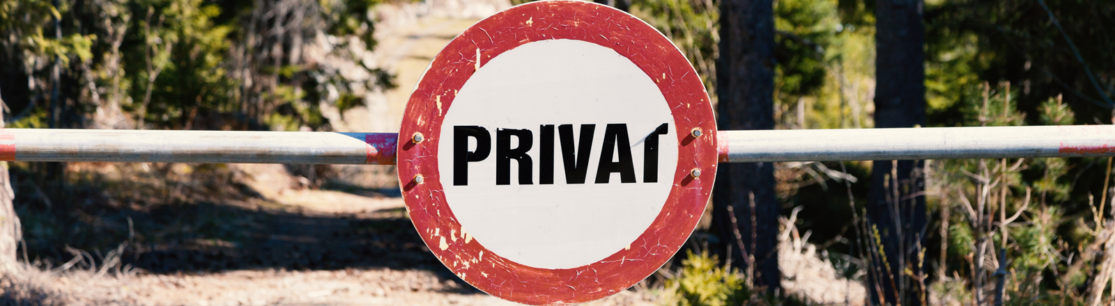 """Ein Waldweg, der mit einer Schranke versperrt ist. An der Schranke ist ein Schild mit der Aufschrift """"Privat"""" angebracht."""