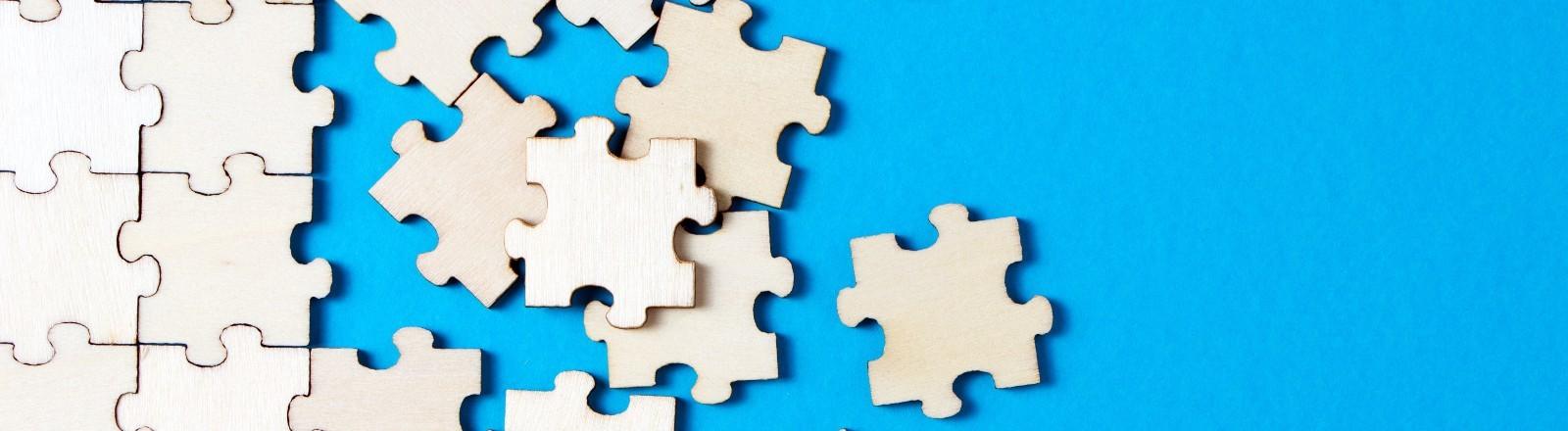 weißes Puzzle vor blauem Grund