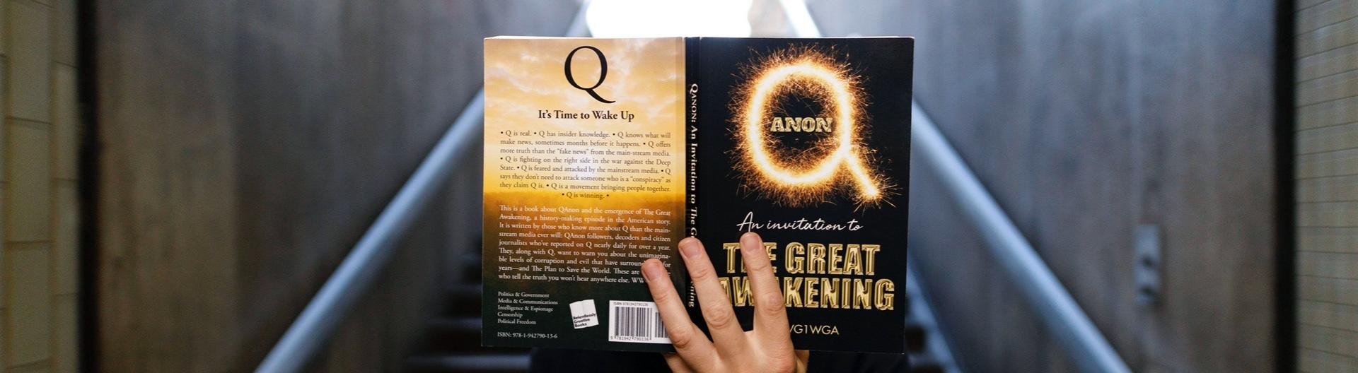 Ein Mann hält sich das Buch QAnon- The great awakening vor das Gesicht, 5.7.20