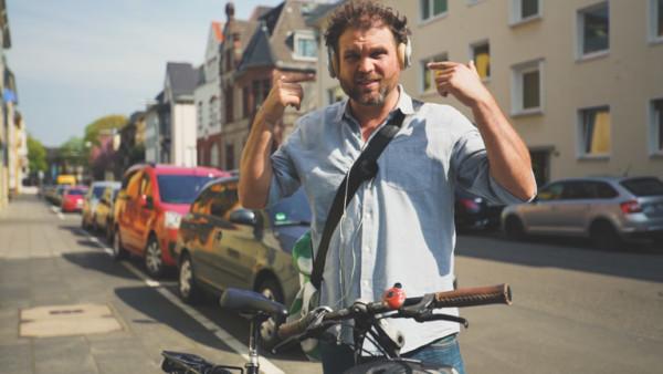 Radreporter Paulus Müller zeigt auf seine Kopfhörer