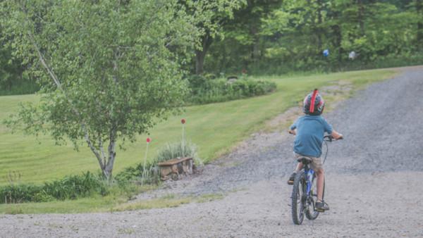 Kind fährt auf Landstraße mit Fahrrad
