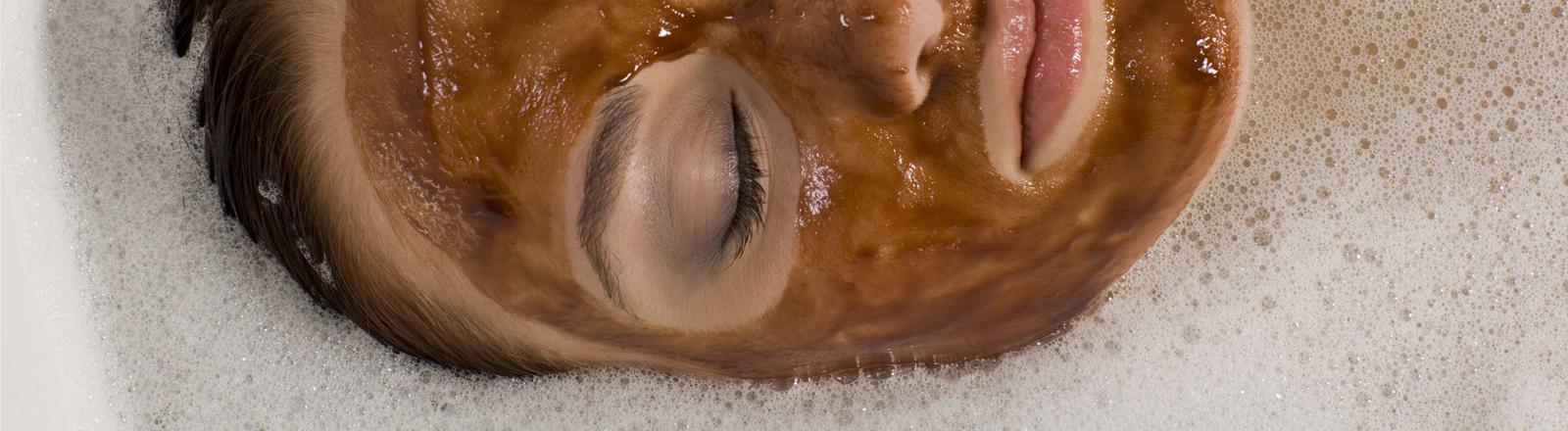 Frau mit Gesichtsmaske in der Wanne