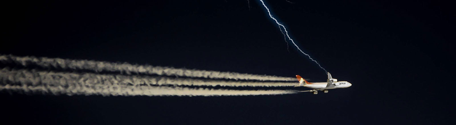 Ein Flugzeug, dass auf einen Blitz zufliegt