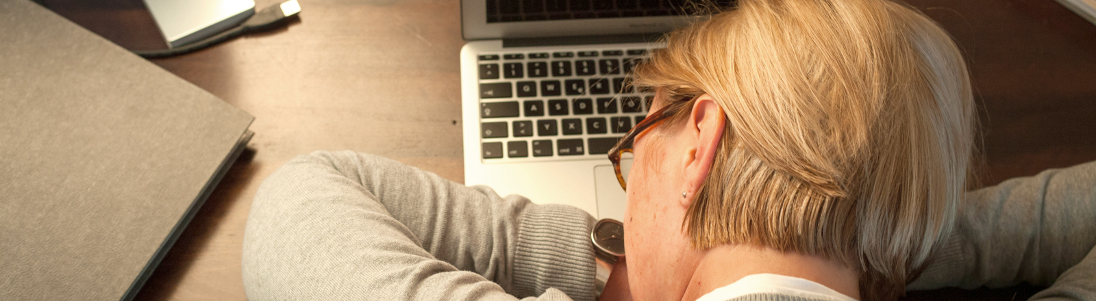 Eine Frau schläft auf ihrem Rechner.