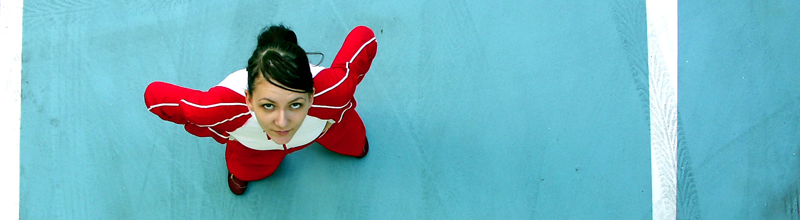 Ein Frau mit roten Anzug steht da und guckt resolut nach oben.