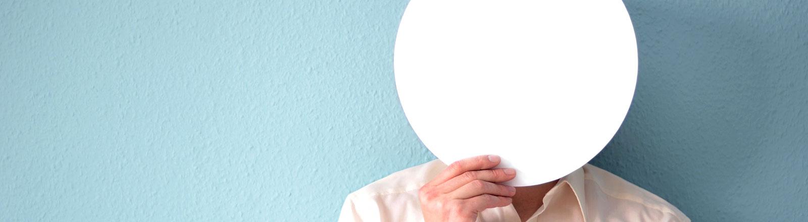 Eine Person hält sich eine weiße Scheibe vor das Gesicht.
