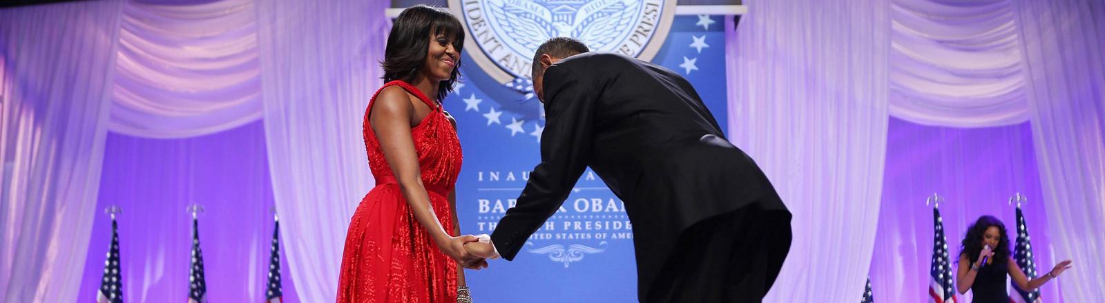 Barack Obama verneigt sich vor seiner Frau Michelle.
