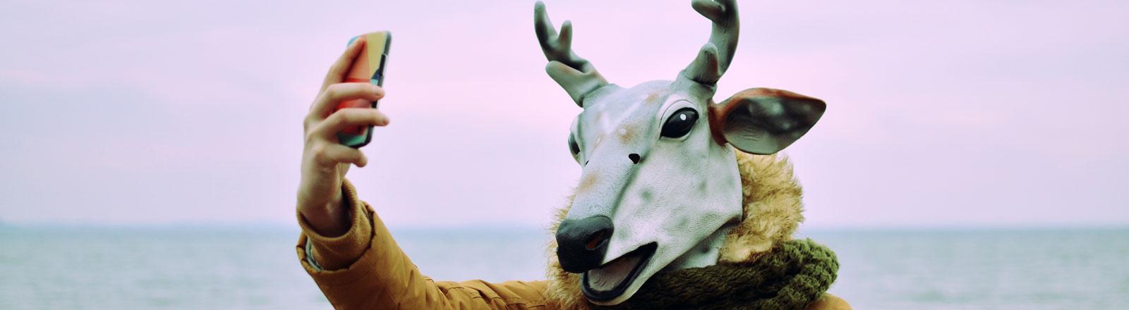 Eine Person hat eine Hirschmaske auf dem Kopf und macht ein Selfie.