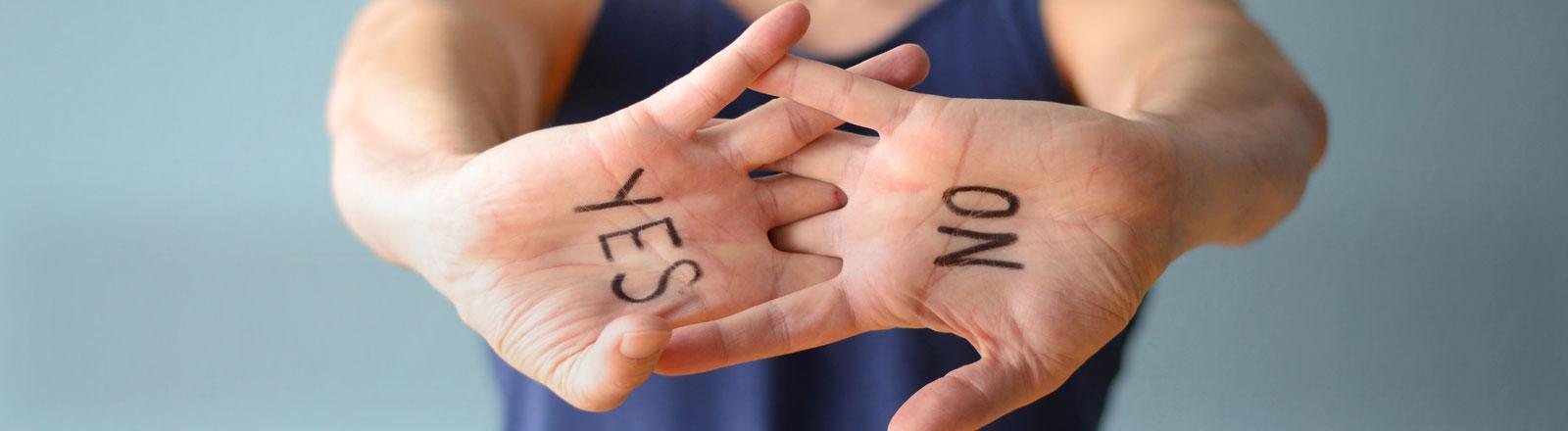 Eine Person zeigt ihre Handinnenflächen. Auf der einen steht: Yes, auf der anderen: No