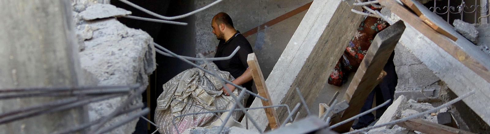 Ein Mitglied der palästinensischen Familie Abu Lealla trägt Sachen aus seinem zerstörten Haus in Gazastadt.