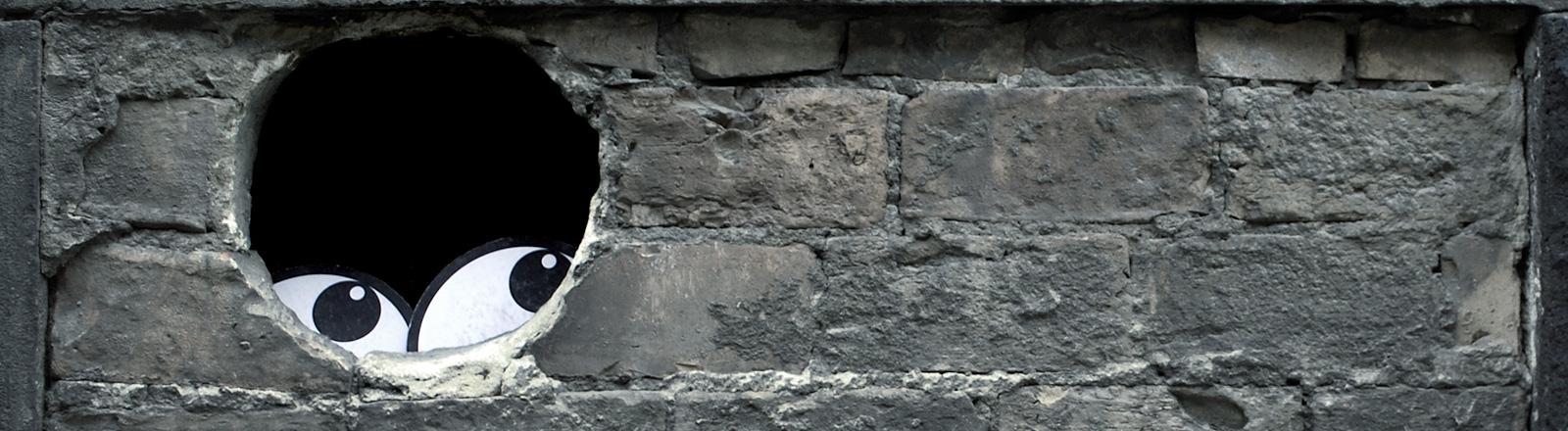 Zwei Augen, die in einem Loch in der Wand durchschauen.