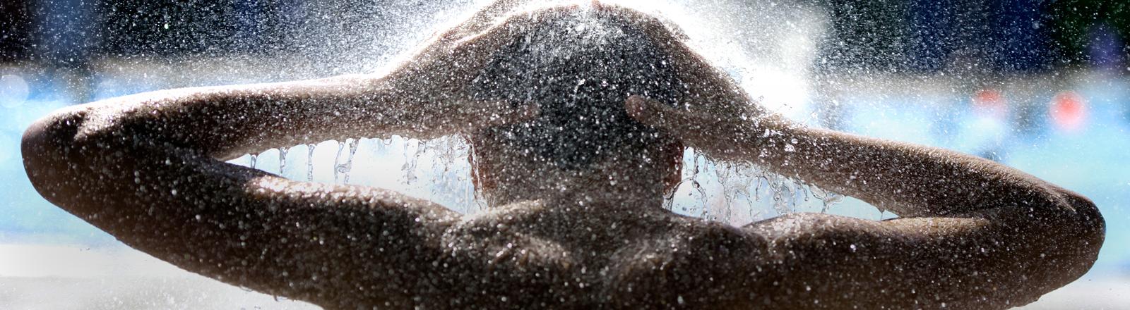 Ein Junge steht unter der Dusche.